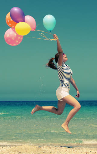 girl running on beach with balloon